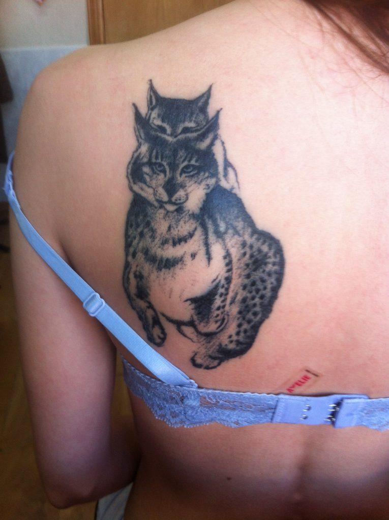 Татуировка на лопатке у девушки в виде двух рысей